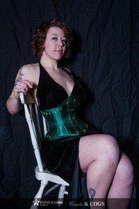 Model seated on a chair and wearing a green satin corset
